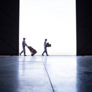 Two couriers working together to deliver parcels and boxes outside a warehouse door